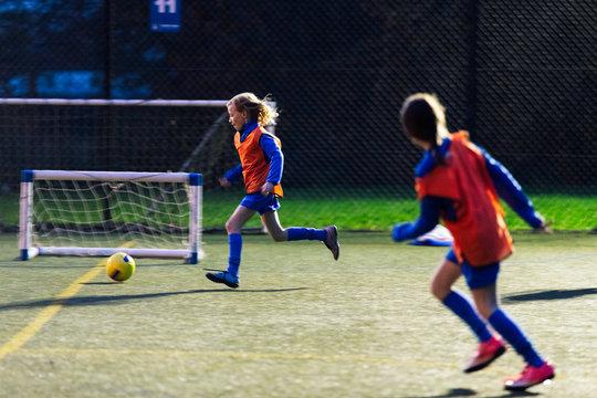 Girls running, playing soccer on field