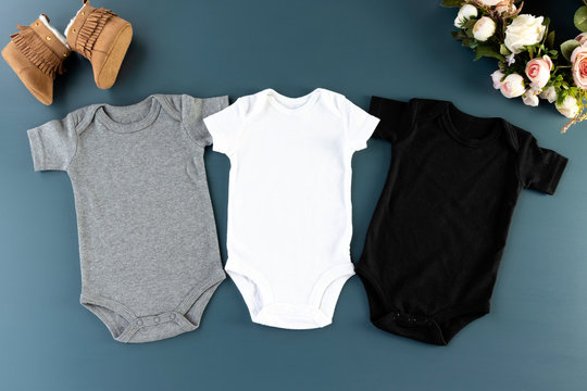 Three baby bodysuits on a blue background mockup - 3 baby grows flat lay (white, grey & black)