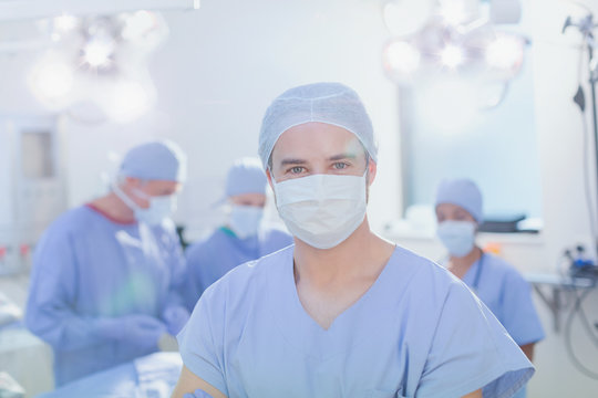 Portrait confident young male surgeon wearing surgical mask in operating room