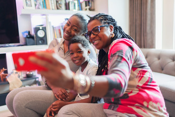 Multi-generation family taking selfie with camera phone in living room