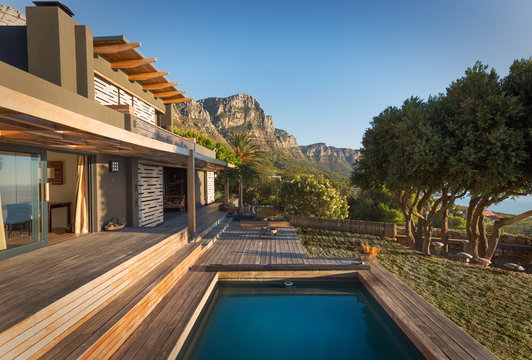Mountains in background of luxury home showcase exterior house with swimming pool