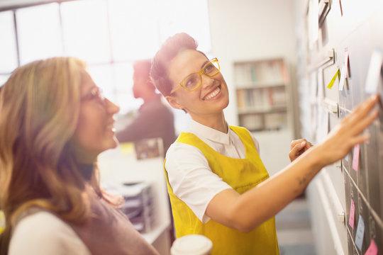 Smiling, confident creative businesswomen planning, brainstorming at blackboard