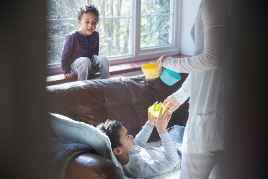 Mother giving snacks to children in living room