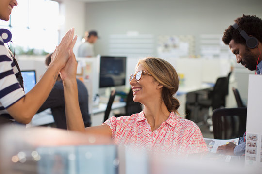 Enthusiastic, confident businesswomen high-fiving in office