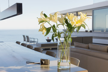 Yellow lily bouquet in vase on modern, luxury home showcase interior dining table next to digital camera