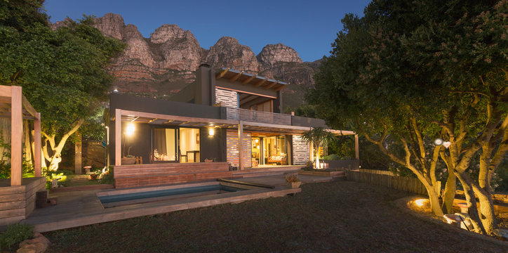 Mountains behind illuminated modern, luxury home showcase exterior house at night