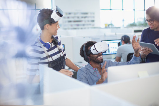 Computer programmers testing virtual reality simulators in office