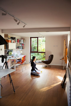 Young woman meditating in home office