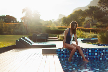Woman in bathing suit relaxing at luxury swimming pool