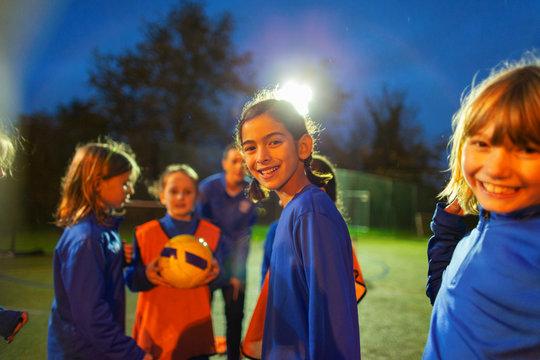 Portrait smiling girls soccer team on field at night