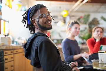 Portrait smiling young man with headphones at kitchen table