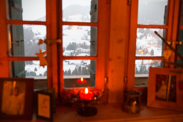 Christmas candle in window overlooking tranquil snowy landscape, Forclaz, Switzerland