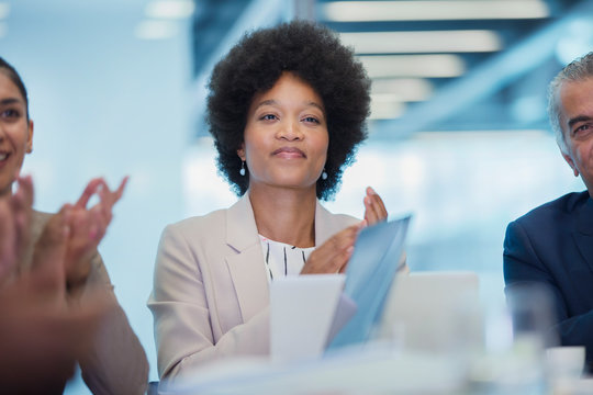 Confident businesswoman clapping in conference room meeting