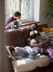 Father and children relaxing, cuddling on living room sofa