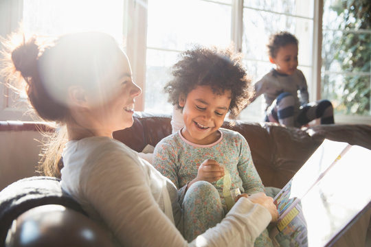 Mother and daughter reading book on sofa in living room