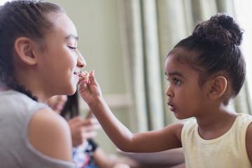 Cute toddler girl applying lip gloss to sister s lips