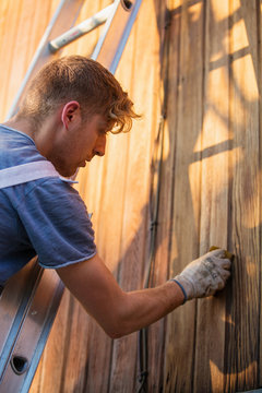 Male worker on ladder staining wood siding on home exterior