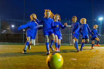 Girls soccer team playing, running toward ball on field at night