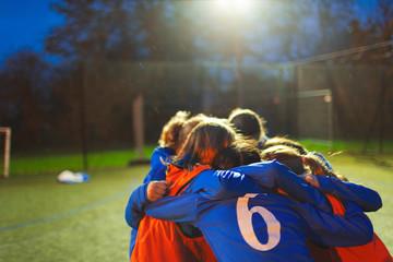 Girls soccer team huddling on field at night
