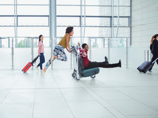 Playful couple pushing luggage cart in airport