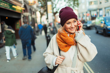 Young woman in stocking cap and scarf talking on smart phone on urban sidewalk