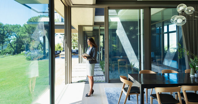 Confident businesswoman working from home, standing in corridor