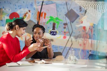 Female engineers examining prototype in creative conference room