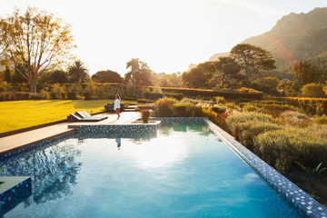 Woman walking at sunny, idyllic poolside, Cape Town, South Africa