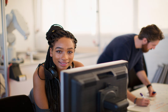 Portrait confident female engineer working at computer in office