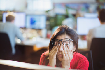 Tired, stressed businesswoman rubbing eyes in office