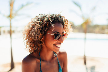 Happy young woman in sunglasses on sunny beach