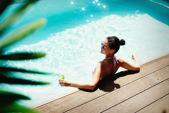 Woman relaxing with cocktail in sunny summer swimming pool