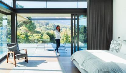 Woman talking on smart phone in patio doorway of modern, luxury bedroom