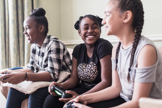 Carefree tween girl friends playing video game