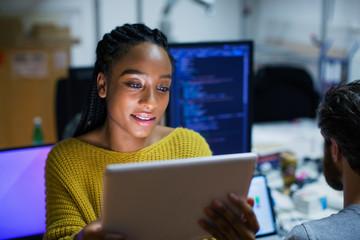 Female computer programmer using digital tablet in office