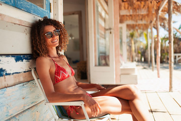 Portrait carefree young woman in bikini relaxing on beach hut patio