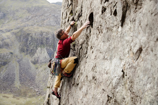 Focused male rock climber scaling rock face