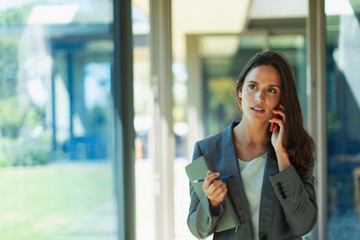 Businesswoman talking on cell phone in corridor