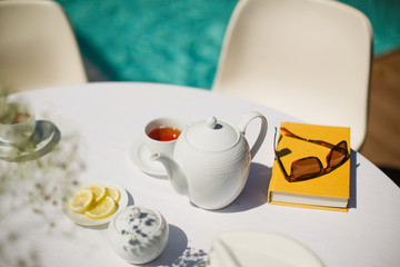 Tea service and book on sunny poolside table
