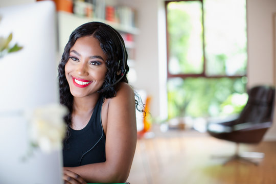 Happy young woman with headset working from home at computer