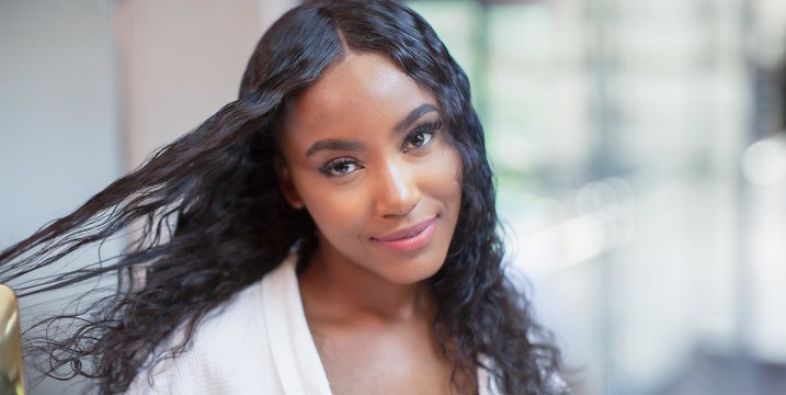 Portrait confident beautiful young woman brushing long black hair