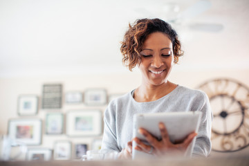 Smiling woman using digital tablet Wall mural