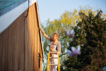 Male painter on ladder painting home exterior trim