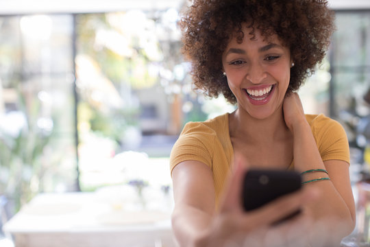 Playful happy young woman taking selfie with camera phone