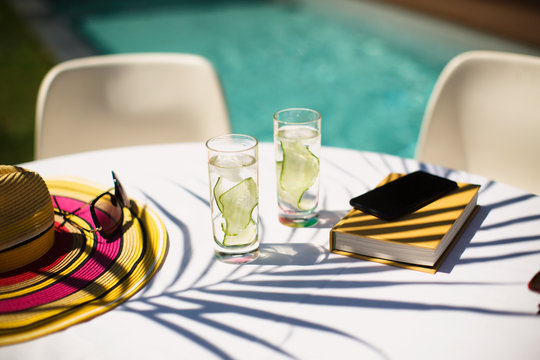 Cucumber water and book on sunny summer poolside table
