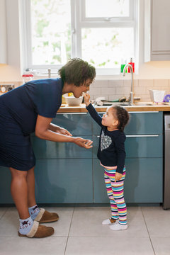 Cute daughter feeding pregnant mother in kitchen