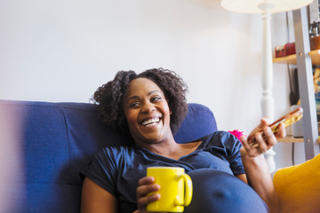 Laughing pregnant woman with tea and smart phone on sofa