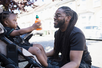 Father talking to toddler son in stroller on urban sidewalk