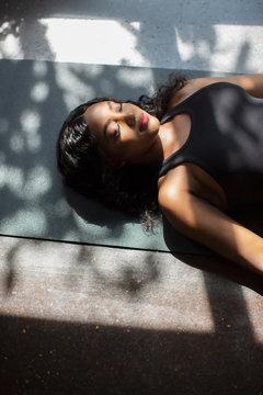 Serene young woman laying on yoga mat