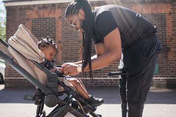 Father fastening toddler son in stroller on sunny sidewalk